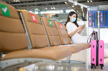 A traveller woman is wearing protective mask in International airport, travel under Covid-19...