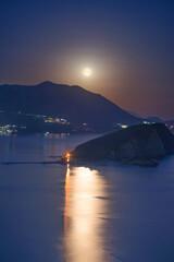 Full moon rise above Budva Riviera, Saint Nicholas island and Adriatic littoral, night cityscape, Montenegro, Europe. Famous tourist landmark and destination. Vertical landscape.