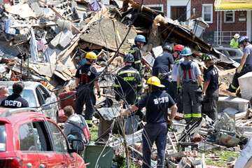 Rescue workers stand on the debris of a destroyed building after an explosion in a residential area of Baltimore