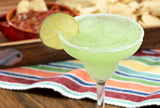 Frozen margarita garnished with lime slice, out of focus red salsa and corn chips in background