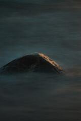 kamień w morzu i lekko oświetlony o wschodzie słońca