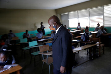 Assistant principal Sauveur Louissaint, wearing a face mask, to prevent the spread of the coronavirus disease (COVID-19), checks that pupils keep social distance at a classroom during the first day of school after holidays, in Port au Prince