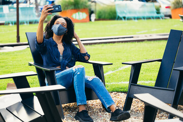 Black woman sitting in patio chair by outdoor fire pit with a mask taking a selfie during covid 19