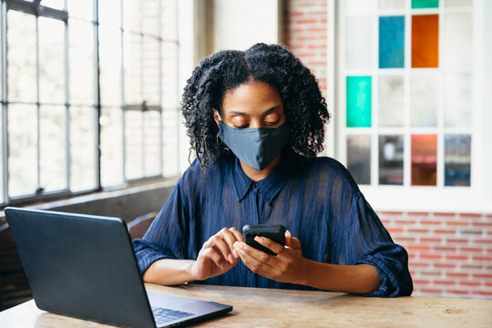 Black woman working at cafe on laptop and phone with face mask during covid-19