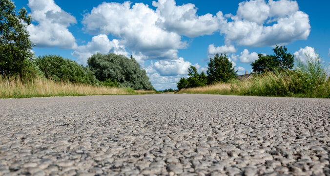 Panoramic rural landscape. Leading forward country road in summer.