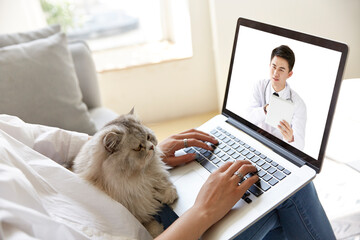 young asian woman talking to doctor via video call using laptop computer