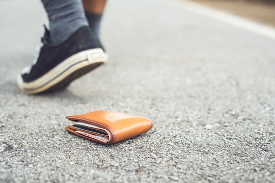 Man lose brown wallet on the road in tourist attraction. Losing wallet concept. Focus on wallet