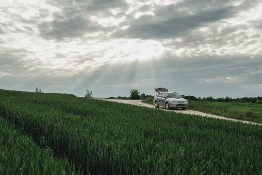 TERNOPIL, UKRAINE - July 11, 2020: Subaru Outback Diesel on the Country Road on the Green Field