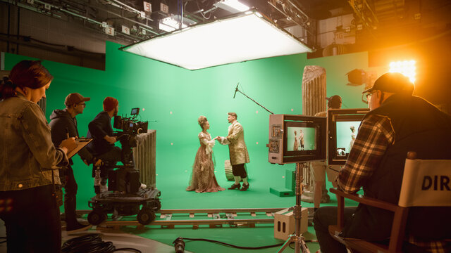 On Set: Famous Female Director Controls Cameraman Shooting Green Screen Scene with Two Actors Talented Wearing Renaissance Clothes Talking. Crew Shooting Period Costume Drama Movie.