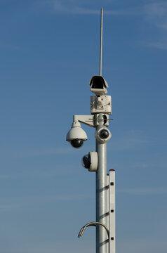 Electronic cctv security camera, surveillance camera on top of pole on blue sky background