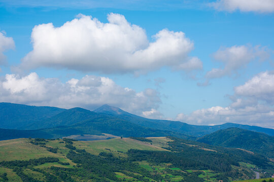 Carpathian countryside in September. mountain landscape on a sunny day. trees on the meadow. sky with fluffy clouds