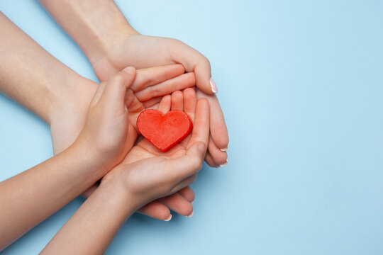 Human hands holding, giving heart isolated on blue background with copyspace. Concept of emotions, feelings, charity, family, supporting hand. Thankful, inspirational. Romantic and togetherness.