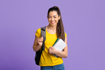 Education Concept. Asian student girl with workbooks and backpack smiling to camera