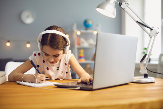 Online education for children. A girl in headphones makes an online lesson using a computer video call to a virtual teacher at home.