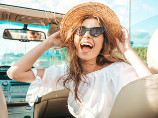 Portrait of young beautiful and smiling hipster girl in convertible car. Sexy carefree woman...