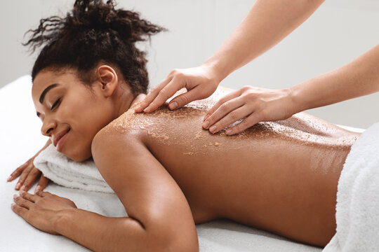Spa therapist scrubbing black woman skin, using natural beauty products