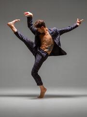 Cool young man dancer dancing expressive dance in suit in studio. Dance school poster. Dance lessons