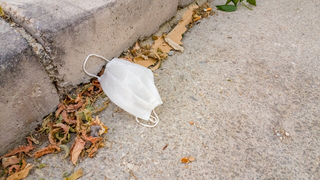 White surgical mask thrown away on the street after use