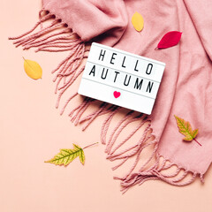 Lightbox with Hello Autumn text on pastel background. Cozy draped scarf and leaves