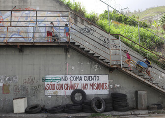 Children carry plastic containers to be filled with water that accumulated at a stalled tunnel construction project near El Avila mountain that borders the city of Caracas