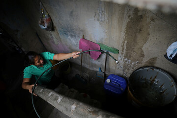Maria fills a metal bin with water inside her house via a community-made pipe system that extract water that accumulated at a stalled tunnel construction project near El Avila mountain that borders the city of Caracas