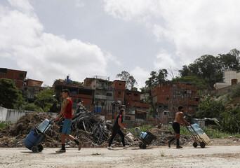People carry plastic containers filled with water that accumulated at a stalled tunnel construction project near El Avila mountain that borders the city of Caracas
