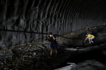 Men wearing protective masks carry a plastic pipe inside a stalled tunnel construction project near El Avila mountain that borders the city of Caracas