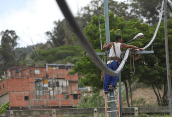 A man works on a pipe from a community-made water system that bring water that accumulated at a stalled tunnel construction project near El Avila mountain that borders the city of Caracas