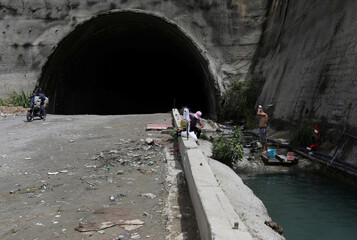 People use water that accumulated at a stalled tunnel construction project near the imposing El Avila mountain that borders the city of Caracas