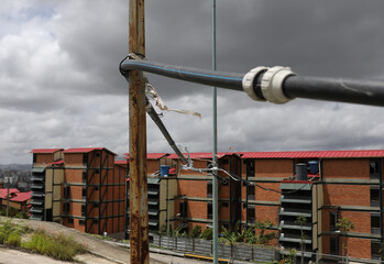 A pipe feed a public housing building from water that accumulated at a stalled tunnel construction project near El Avila mountain that borders the city of Caracas