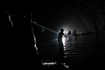 Men pull a rope inside a stalled tunnel construction project near El Avila mountain that borders the city of Caracas