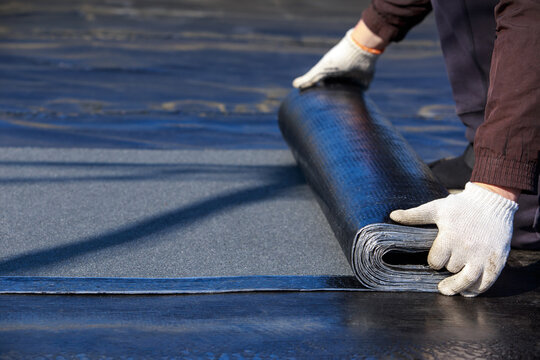 Worker puts roofing material