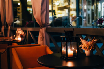 Blurred night interior of street cafe. Summer terrace, romantic atmosphere