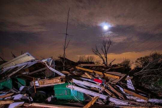 Tornado damage piles up at night
