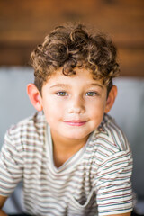 Handsome young boy with curly hair smiling.