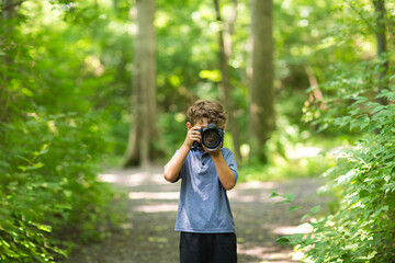 Young boy taking photo in the forest.