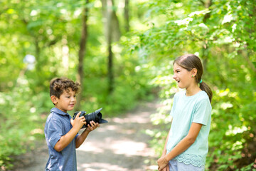 Young boy taking photo of his sister in the forest.