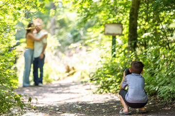 Little boy taking photo of his parents in the woods.