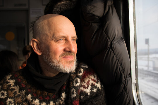Mann m besten Alter schaut aus einem Zugfenster in die Wintersonne