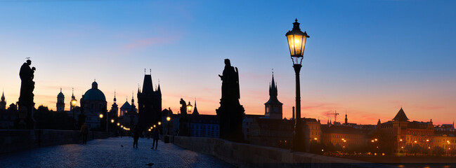 Fotomurales - Charles Bridge at dawn. Panoramic image, silhouette of Bridge Tower and sculptures, street lights in Prague, Czech Republic.