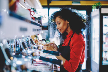 Professional female barista with dark skin standing at bar on working place and preparing tasty beverage on order.Experienced african american young woman waitress using modern coffee machine