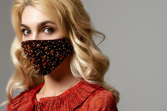 Woman wearing stylish dark red velvet protective face mask with golden rhinestones, beads. Fashion accessory during quarantine of coronavirus. Close up studio portrait. Copy, empty space for text