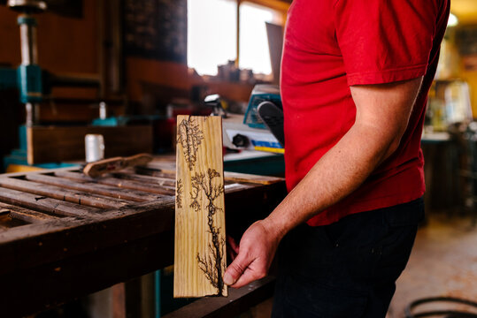 Side view of crop male pyrographer standing in workshop and demonstrating amazing woodwork decorated with burn marks