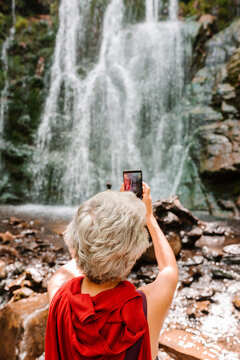 Back view of faceless female tourist with gray hair using smartphone and taking picture of magnificent waterfall during summer adventure