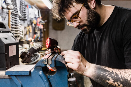 Side view of concentrated male mechanic with tattoos using vise and repairing red back lamp of motorbike while working in workshop