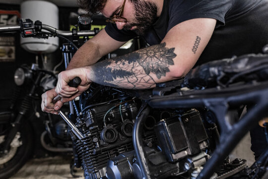 Side view of crop male mechanic using socket wrench and fixing motorbike in workshop