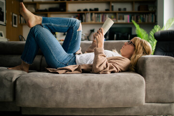 Side view of pensive female in casual wear lying on sofa at home and enjoying interesting novel while relaxing during weekend