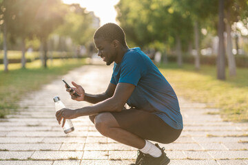 African black man in sports clothes sitting down and taking selfie in the park