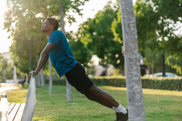 African athletic black man in sport clothes stretching in the park using a bench on a sunny day