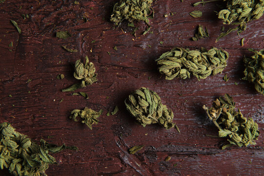 Dried cannabis buds on wooden table